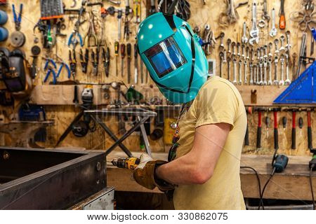 A Blacksmith Looks Towards Camera Whilst Wearing A Protective Welding Mask And Drilling Steel. Skill