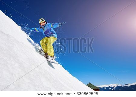 Guy Snowboarding Down The Mountain Slope. Portrait Of Young Man Snowboarding In Winter Against Blue