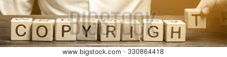 Businessman Puts Wooden Blocks With The Word Copyright. Patenting. Copyright Protection. Brand And P