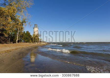 The Historic Pelee Island Lighthouse, Built In 1833, Reflecting On Its Lake Erie Shoreline In Autumn