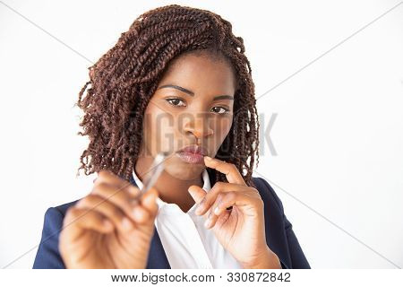 Focused Female Manager Holding Marker, Writing On Glass Board. Young African American Business Woman
