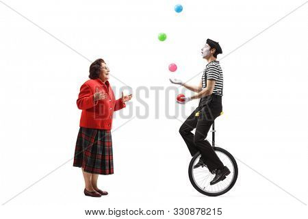 Full length shot of an elderly lady looking at a mime juggling on a unicycle isolated on white background