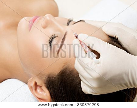 Portrait of young Caucasian woman getting cosmetic injection in forehead. Beautiful woman gets injection in her face.
