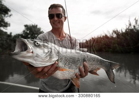 Amateur angler stands in the boat, smiles and holds the trophy Asp fish (Leuciscus aspius)