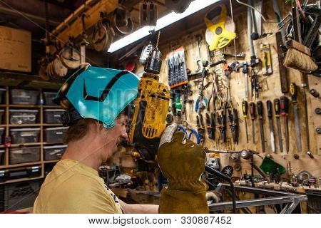 A Closeup View Of A Blacksmith Holding An Electric Drill Inside His Workshop. Skilled Tradesman Wear
