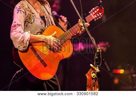 A Close Up View On A Stylish Lady Band Member Playing A Guitar During A Live Music Set. Blurred Musi