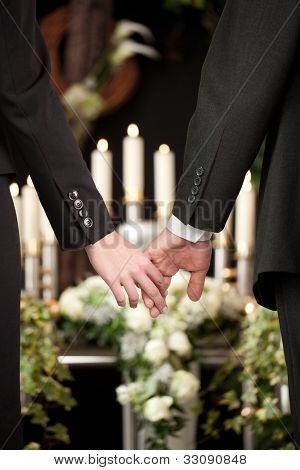 Religion, death and dolor  - couple at funeral holding hands consoling each other in view of the loss
