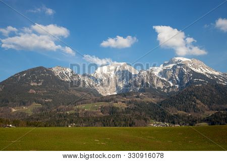 Idyllic Landscape Scenery With Trees And Mountains With Snowcapped Mounaintops At Berchtesaden Germa