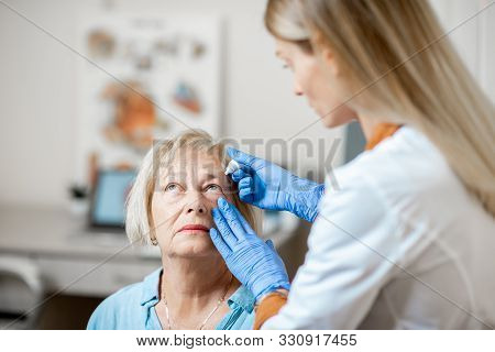 Female Doctor Dripping Eye Drops On Eyes Of A Senior Patient During A Treatment At The Ophthalmologi