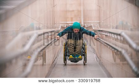 Disabled Man In Wheelchair Getting Up On The Long Special Ramp Leaning On The Railing