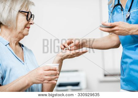 Nurse Giving Some Medicine For A Senior Woman Sitting On The Couch, Taking Care Of Elder Patients In