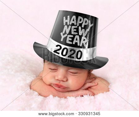 Newborn baby girl wearing a Happy New Year 2020 hat.