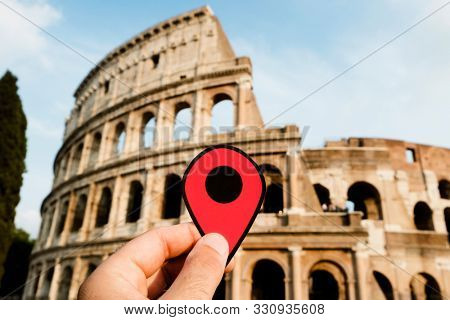 closeup of the hand of a caucasian man holding a red marker at the famous Flavian Amphitheatre or Colosseum, in Rome, Italy