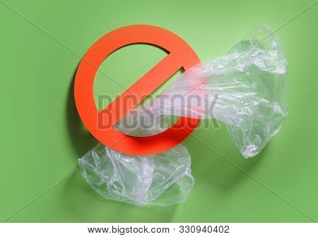 Empty plastic bag in a stop sign on green background. Concept of stop plastic pollution, global warming, recycling plastic, plastic free.