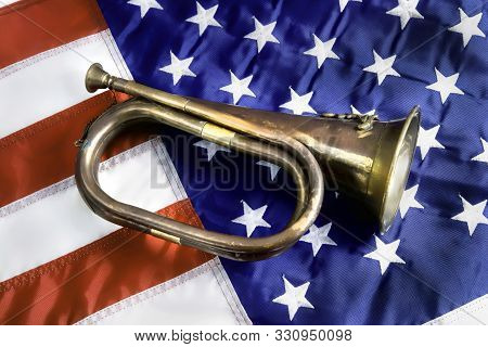 Old Brass Bugle On The American Flag.