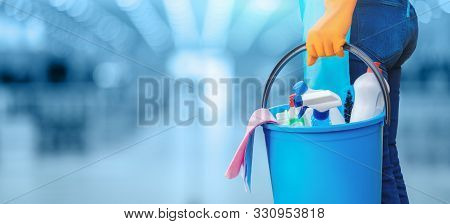 Concept Of Quality Cleaning. The Cleaning Lady Standing With A Bucket And Cleaning Products.