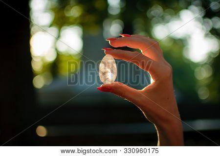 Female Hand With Transparent Amethyst Quartz Yoni Egg For Vumfit, Imbuilding Or Meditation. Shining