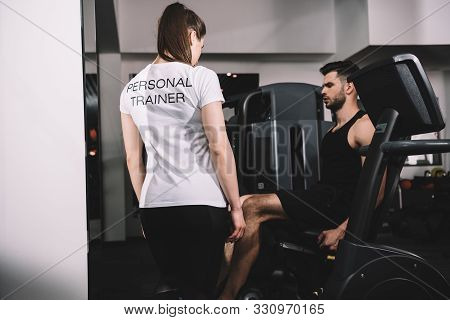 Back View Of Personal Trainer Instructing Handsome Sportsman Working Out On Recumbent Elliptical Tra