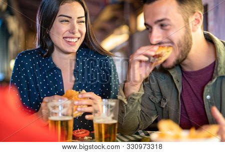 Couple In Love Having Fun Eating Burger At Restaurant Pub - Young Happy People Enjoying Moment At In
