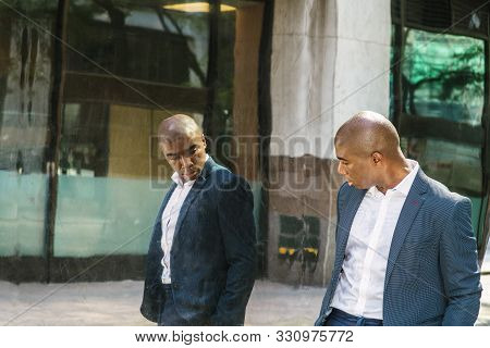 Young African American Man Wearing Blue Blazer, White Shirt, Standing By Metal Mirror On Street In N
