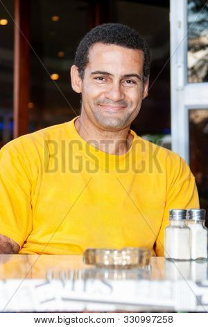 mixed race man in the neighborhood, sitting in the coffeeshop lifestyle portrait