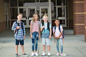 Group of Elementary school students standing in front of their school. Smiling and hanging out together after school. poster