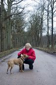 elderly female with her dog during a walk in the forest poster