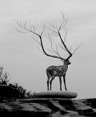 Sculpture of a deer with massive antlers standing on a rock platform poster