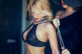Sensual Blonde Shy Woman In Bra Holded By Lesbian Lover On Chain
