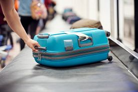 Suitcase on luggage conveyor belt carousel in the baggage claim at airport