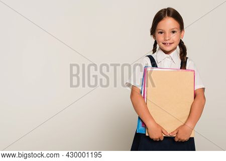 Happy Schoolkid Looking At Camera While Holding Copy Books Isolated On Grey