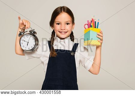 Pleased Schoolkid Showing Pen Holder And Large Alarm Clock Isolated On Grey