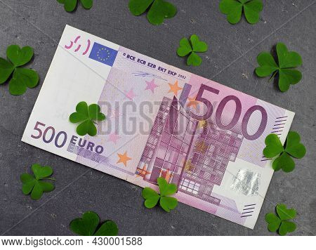 One 500 Euro Bill On Black Slate Plate With Green Clover Leafs, Concept Of Winning Money Or Have Luc
