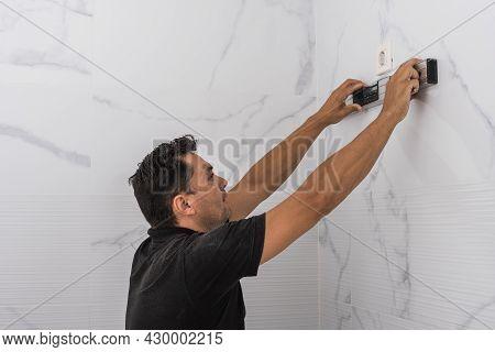 Man Using A Spirit Level On A Kitchen Wall