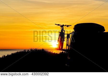 Camper, Recreational Vehicle With Bicycles On Rack Camping On Beach At Sunrise. Holidays And Travel