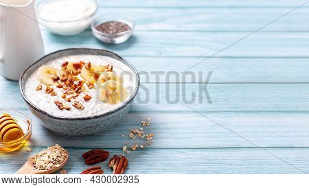 Overnight Oats With Banana And Pecans, Chia Seeds In Bowl With Ingredients Around. Healthy High Prot