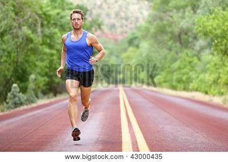Running athlete man. Male runner sprinting during outdoors training for marathon run. Athletic fit young sport fitness model in his twenties in full body length on road outside in nature. poster