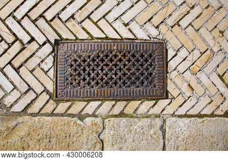 Iron Rusty Rectangular Manhole With Shaped Holes In The Lid On The Sidewalk Paved With Stone Tiles T