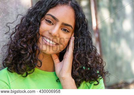 Outdoor portrait of beautiful happy mixed race African American girl teenager female young woman thinking and smiling with perfect teeth