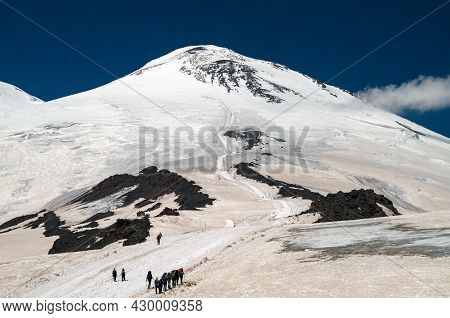 Climbers Go To The Top Of Mount Elbrus.a Group Of Tourists With Backpacks, Walking One After Another