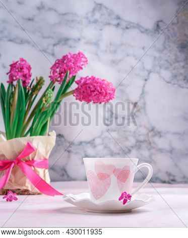 White Cup With Pink Hearts With A Vase Of Spring Flowers On The Table Against The Background Of Gray
