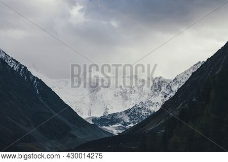 Atmospheric Landscape With High Snowy Mountain Wall And Glacier In Valley Among Dark Silhouettes Of