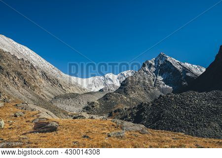 Autumn Landscape With Highland Valley Among Snow-covered Mountain Range And Pointy Peak Under Blue S