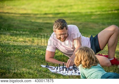 Strategic And Tactic. Tutorship. Dad And Boy Play Logic Game. Father And Son Playing Chess