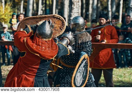 An Epic Battle Of Knights In Armor And Helmets. Sword Fighting. Reconstruction Of Medieval Battles.