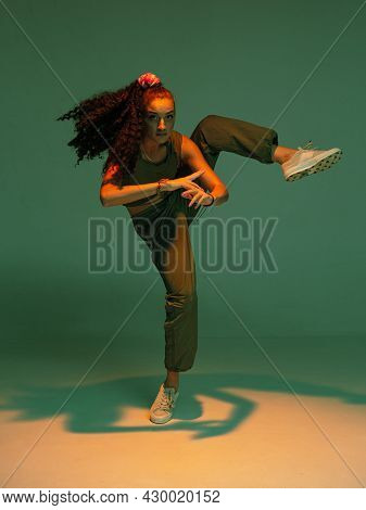 Dancing Mixed Race Girl With Afro Hairs Performing Expressive Hip Hop Dance In Colourful Studio Ligh
