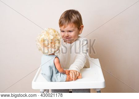 Baby Toddler Plays With Old-fashioned Doll On A Studio Shot. Funny Serious Face. Best Friend Toy. Ro