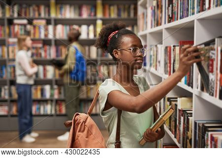 Waist Up Portrait Of Female Africa-american Student Choosing Books In College Library, Copy Space