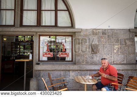 Ljubljana, Slovenia - June 15, 2021: Man, Middle Aged Male, Drinking Coffee Alone At The Terrace Pat