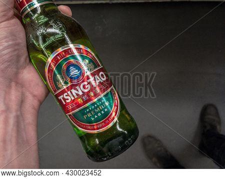 Belgrade, Serbia - June 6, 2021: Hands Holding A Bottle Of Tsingtao Beer. Tsingtao Beer Is A Brand O
